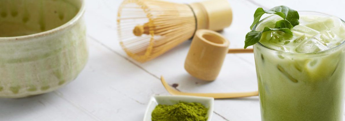 Iced Matcha Latte Tea and homemade tea brewing accessories with bamboo whisk, green tea powder on white wooden background.